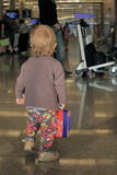 Unaccompanied baby in airport. Unaccompanied baby with small case standing in the airport and looking forward Stock Photography