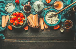 Unadulterated italian strawberry tiramisu cooking ingredients on dark rustic kitchen table Royalty Free Stock Photos