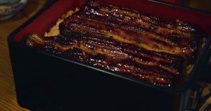 Unagi, anguila asada a la parrilla, sirvió estilo del donburi en el arroz en una caja de la laca almacen de metraje de vídeo