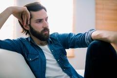 Unahppy man som tänker på hans soffa Royaltyfri Bild