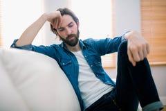 Unahppy man som tänker på hans soffa Fotografering för Bildbyråer