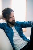 Unahppy man som tänker på hans soffa Royaltyfria Bilder