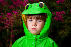 Unamused Boy in Frog Raincoat Looks at Camera. A little boy in a frog raincoat looks unamused at the camera.  He has rain drops all over his coat and it is a Royalty Free Stock Image
