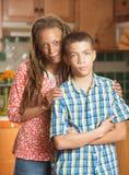 Unangenehmer jugendlich Junge steht, Gesicht verziehend neben seiner liebevollen Mutter Stockfotografie