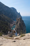 Unapproachable rock in the sea and tourists.  Royalty Free Stock Photography