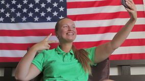 Unated states flag. Beautiful girl use a smartphone makes photo. American flag. A girl reading a book on a background of the American flag, USA stock video footage