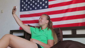 Unated states flag. Beautiful girl use a smartphone makes photo stock video