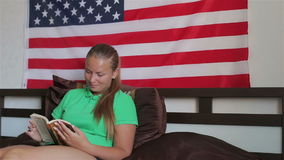 Unated states flag. A girl reading a book stock video