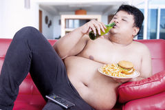 Unattractive overweight man on the red couch Stock Images