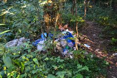 Unauthorized landfill in the forest. Pollution of nature. Bad ecology stock photography