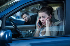 Unaware of the danger. Shot of a young concerned women talking on the phone in her car and a men touching a car window behind her back Royalty Free Stock Photos