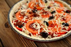 Unbacked tomato tart with olives selective focus on wooden backg Royalty Free Stock Images