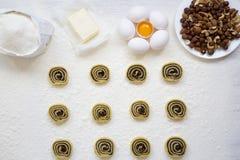 Unbaked μπισκότα με τους σπόρους, τις σταφίδες και τα καρύδια παπαρουνών στον άσπρο ξύλινο πίνακα Συστατικά για την κατασκευή των Στοκ Εικόνα