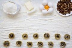 Unbaked μπισκότα με τους σπόρους, τις σταφίδες και τα καρύδια παπαρουνών στον άσπρο ξύλινο πίνακα Συστατικά για την κατασκευή των Στοκ Εικόνες
