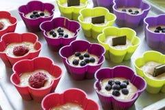 Unbaked bananmuffin med chokladstänger, blåbär, jordgubbar, muttrar och russin i färgsilikonformer arkivfoto