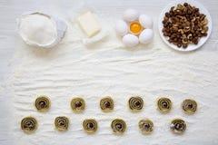Unbaked ciastka z makowymi ziarnami, rodzynkami i dokrętkami na białym drewnianym stole, Składniki dla robić ciastku Odgórny wido zdjęcia stock