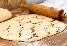 Unbaked donuts of dough with flour. Ball of raw dough, rolling pin and cut out circles from raw cookie dough rolled seam on a wooden board Stock Photography