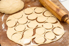 Unbaked donuts of dough with flour. Ball of raw dough, rolling pin and cut out circles from raw cookie dough rolled seam on a wooden board Royalty Free Stock Photos
