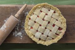 Unbaked pie with rolling pin on wooden surface. A unbaked pie on a wooden surface on a green table next to a rolling pin and some spilled flour royalty free stock photography