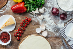Unbaked pizza dough with fresh ingredients on wooden table. Top view of unbaked pizza dough with fresh ingredients on wooden table Stock Photography