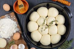 Unbaked soft and fluffy dinner buns. In baking dish with dough, flour and egg on a cutting board, olive oil, rolling pin on wooden kitchen table, view from Royalty Free Stock Photo