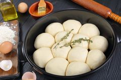 Unbaked soft and fluffy dinner rolls. In baking dish with dough, flour and egg on a cutting board, olive oil, rolling pin on wooden kitchen table, view from Royalty Free Stock Image
