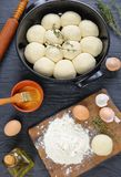 Unbaked soft and fluffy dinner rolls. In baking dish with dough, flour and egg on a cutting board and rolling pin on wooden kitchen work top, vertical view from Royalty Free Stock Images