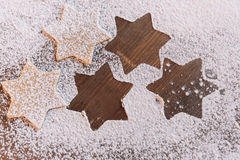 Unbaked star shaped cookies in flour on table. `Close-up top view of unbaked star shaped cookies in flour on table Stock Image