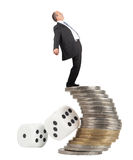 Unbalanced business man. On a top of coins pile -concept of business risk stock photography