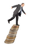 Unbalanced businessman. Unbalanced business man on a top of coins pile -concept of business uncertainty stock image