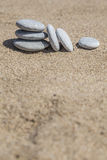 Unbalanced stones on sand Stock Photos