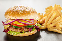 Unbearable desire. A closeup of a tempting tasty burger with red onion and vegs along with yummy french fries Royalty Free Stock Images