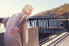 Elderly woman touching her sore small of the back. Unbearable pain. White-haired elderly lady standing on the bridge and touching her sore waist while suffering Royalty Free Stock Photo