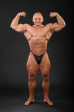 Unbearbeiteter Bodybuilder demonstriert Armmuskeln Lizenzfreies Stockfoto