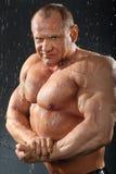 Unbearbeiteter Bodybuilder steht im Regen Stockbild