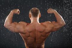 Unbearbeiteter Bodybuilder steht im Regen Lizenzfreies Stockbild