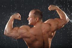 Unbearbeiteter Bodybuilder steht im Regen Lizenzfreie Stockfotos