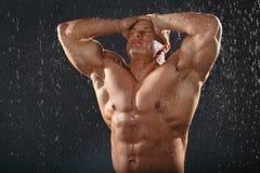 Unbearbeiteter gebräunter Bodybuilder im Regen Stockfotografie