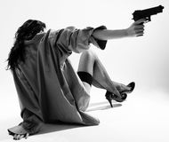 Unbearbeitetes Mädchen sitzt zurück und zielt mit Pistole Stockfotografie