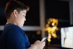 Unbeaufsichtigter Junge, der am Handy nachts plaudert und schreibt lizenzfreie stockfotos
