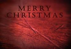Unbedeutender hölzerner Hintergrund mit Weihnachtsgruß lizenzfreie stockbilder