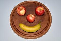 Unbedeutendes rundes Fruchtgesicht gemacht vom Apfel, vom Pfirsich und von der Banane lizenzfreies stockfoto