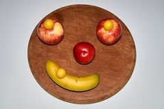 Unbedeutendes rundes Fruchtgesicht gemacht vom Apfel, vom Pfirsich und von der Banane lizenzfreie stockbilder