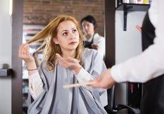Unbefriedigte Blondine sind durch Haarschnitt umgekippt Lizenzfreie Stockbilder
