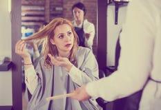 Unbefriedigte erwachsene Frau ist durch ihren Haarschnitt umgekippt Stockfotos