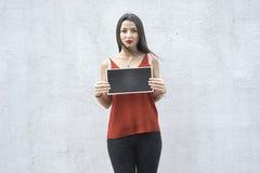 Unbefriedigte Frau, die eine Platte hält lizenzfreie stockfotos