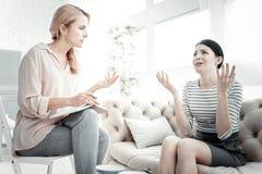 Unbefriedigte unglückliche Frau, die Hände sitzt und rüttelt Stockbilder