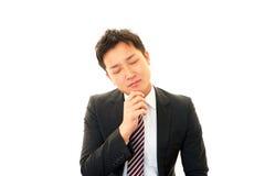 Unbefriedigter asiatischer Geschäftsmann Stockfoto