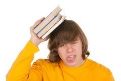 Unbefriedigter Jugendlicher mit Buch Stockfoto