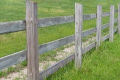 Unbegrenzter Zaun mit grünem Gras Stockfotos